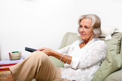 Senior woman using remote control while relaxing on armchair at home Stock Photography