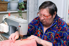 Senior woman using sewing machine Royalty Free Stock Images