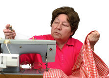 Senior woman using sewing machine at home Stock Images