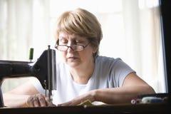 Senior Woman Using Sewing Machine Stock Images