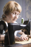 Senior Woman Using Sewing Machine Stock Photography
