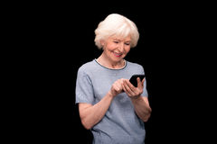 Senior woman using smartphone. Portrait of smiling senior woman using smartphone isolated on black Royalty Free Stock Image