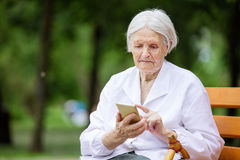 Senior woman using smartphone while sitting on bench in park Royalty Free Stock Image