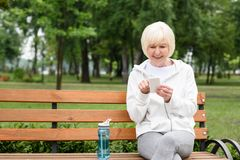 Senior woman using smartphone while sitting on bench with sport bottle. Of water royalty free stock image