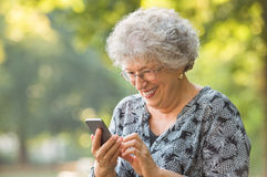 Senior woman using smartphone. Smiling elderly woman wearing spectacles and typing phone message while sitting at park. Cheerful senior woman using wireless Royalty Free Stock Image