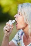 Senior woman using spray against Asthma Royalty Free Stock Photo