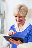 Senior woman using tablet computer at home Royalty Free Stock Photos