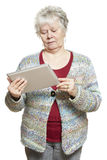 Senior woman using tablet computer looking confused. On white background Royalty Free Stock Images