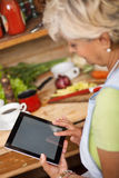Senior woman using tablet in her kitchen stock photos