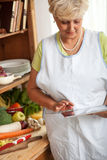 Senior woman using tablet in her kitchen Stock Photo