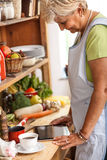 Senior woman using tablet in her kitchen stock images