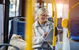 Senior woman using tablet, while riding public bus stock images