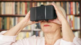 Senior woman using VR 360 glasses at home. Active modern elderly people. Bookshelves in background. Senior woman using VR 360 glasses at home. Active modern stock video footage