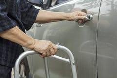 Senior woman using a walker at car park Stock Images