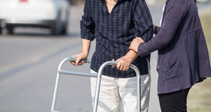 Senior woman using a walker cross street. With assistance stock image