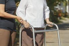Senior woman using a walker cross street Stock Photography