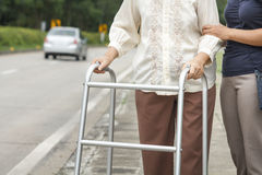 Senior woman using a walker cross street. With assistance stock photo