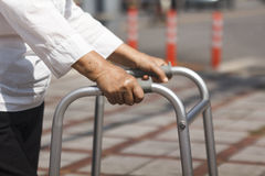 Senior woman using a walker cross street. Stock Image