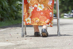 Senior woman using a walker cross street Stock Images