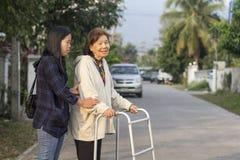Senior woman using a walker cross street. Senior women using a walker cross street with assistance royalty free stock photos