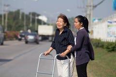 Senior woman using a walker cross street. Senior women using a walker cross street with assistance stock photo