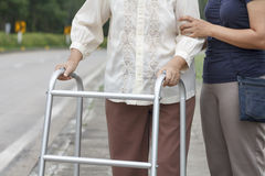 Senior woman using a walker cross street. Senior women using a walker cross street with assistance stock photography