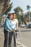 Senior woman using a walker cross street. Senior women using a walker cross street in downtown Stock Image