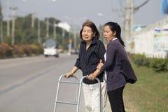 Senior woman using a walker cross street. Senior women using a wheelchair cross street with young assistance stock images