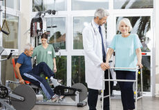Senior Woman Using Walker While Doctor Assisting Her Royalty Free Stock Photos