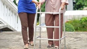 Senior woman using a walker in park stock footage