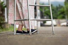 Senior woman using a walker on street. Royalty Free Stock Image