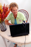 Senior woman using webcam. A senior woman working and using a laptop computer webcam Stock Image