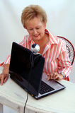 Senior woman using webcam. A senior woman working and using a laptop computer webcam Royalty Free Stock Photography