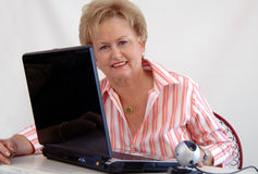 Senior woman using webcam. A senior woman working and using a laptop computer webcam Stock Photos