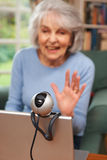Senior Woman Using Webcam To Talk With Family. Senior Woman Uses Webcam To Talk With Family Stock Photo