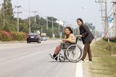 Senior woman using a wheelchair cross street Royalty Free Stock Photography