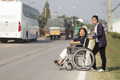 Senior woman using a wheelchair cross street. Senior women using a wheelchair cross street with young assistance royalty free stock images