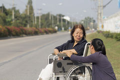 Senior woman using a wheelchair cross street. Senior women using a wheelchair cross street with young assistance royalty free stock photography