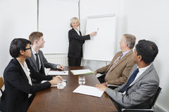 Senior woman using whiteboard in business meeting Royalty Free Stock Photos