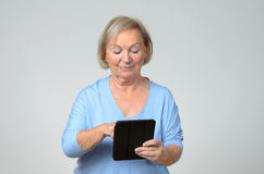 Senior woman using a wireless black tablet PC Royalty Free Stock Image