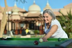 Senior woman on vacation playing billiards Stock Photos