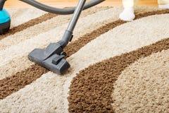 Senior woman vacuuming carpet at home stock photo