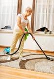 Senior woman vacuuming carpet at home Stock Photos