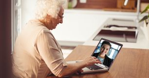 Senior woman video conferencing on laptop Stock Image