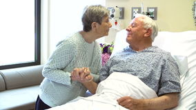 Senior Woman Visiting Husband In Hospital Room. Senior man is pleased to see wife as she visits him in hospital.Shot on Sony FS700 in PAL format at a frame rate stock video