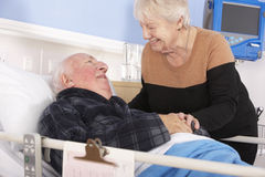 Senior woman visiting husband in hospital Stock Photo