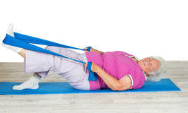Senior woman with vitality exercising. Overweight senior woman full of zest and vitality exercising on a gym mat with her leg raised in the air using a strap for Royalty Free Stock Photography
