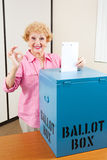 Senior Woman Voting AOkay. Senior woman drops her ballot in the box and gives A Okay sign Royalty Free Stock Photography