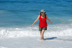Senior woman wading in the ocean at Laguna Beach,  Stock Photo