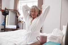 Senior Woman Waking Up And Stretching In Bedroom stock image